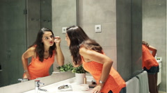 Woman plucking eyebrows with tweezers in front of the mirror in bathroom HD Stock Footage