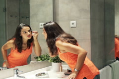 Woman plucking eyebrows with tweezers in front of the mirror in bathroom NTSC Stock Footage