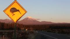 Kiwi road sign and Mount Ngauruhoe at dusk Stock Footage