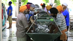 Poor people wash dishes at a soup kitchen in the Golden Temple, Amritsar, India Stock Footage