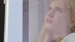 Face of sad tearful girl behind window glass with raindrops Stock Footage