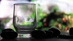 Glass of water on a background of a waterfall - stock footage