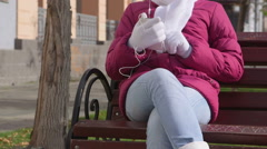 Autumn city scene girl listening music from smart phone on the bench Stock Footage