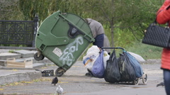 Senior homeless woman picking garbage in dumpster Stock Footage