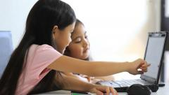 Little cute Asian girl using laptop computer and touching screen - stock footage
