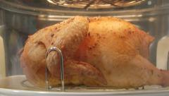 Dolly: whole roasted chicken cooking in i convection countertop oven close-up Stock Footage