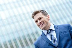 Young smiling man on modern building background - stock photo