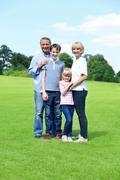 Cute family of four posing to camera Stock Photos