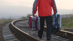Passenger man with suitcases walking away on railway track Stock Footage