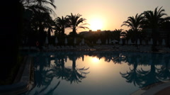 Sunset and Silhouetted Palm Trees Reflected in the Water Stock Footage