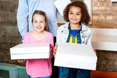 Kids holding pizza boxes Stock Photos