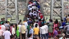 Indian people crossing Laxman Jhula footbridge on river Ganga, Rishikesh, India Stock Footage