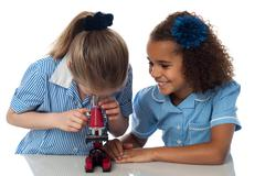 Little girls looking into microscope - stock photo