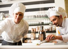 Chef watching his assistant arranging dish Stock Photos