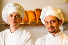 Stock Photo of Young smiling chefs posing in bakery