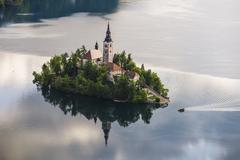 Stock Photo of lake bled boat (pletna) approaching lake bled island at sunrise, gorenjska, s