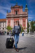 tourist with suitcase, walking past the franciscan church of the annunciation - stock photo