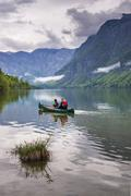 mother and son canoeing on lake bohinj, triglav national park, julian alps, s - stock photo