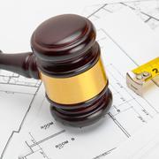 Wooden judge gavel with measure tape above construction blueprint - studio sh Stock Photos