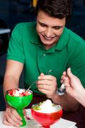 Young guy enjoying tempting dessert - stock photo