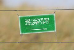border fence - old plastic sign with Saudi Arabia flag - stock photo
