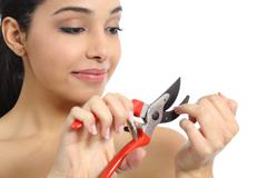 Humorous beautiful woman making manicure with a secateurs - stock photo