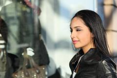 Beautiful woman watching a storefront in the street Stock Photos