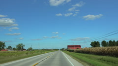 Driving thru farming area passing red barn Stock Footage