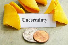 fortune cookie and coins with uncertainty text - stock photo