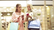 Stock Video Footage of happy women with smartphones and shopping bags