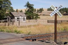 Railroad crossing sign tracks abandoned house rural ranch farmland Stock Photos