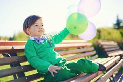 Portrait of a little boy with baloons - stock photo