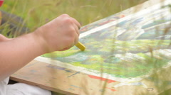 artist sketching nature scene in summer meadow - stock footage