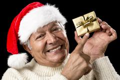 Playful male pensioner pointing at golden gift Stock Photos