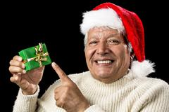 cheerful old man pointing at green wrapped gift - stock photo