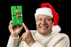 Gleeful aged man pointing at raised green present Stock Photos