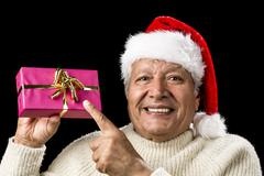 joyous old man pointing at magenta wrapped gift - stock photo