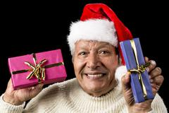 Lighthearted, smiling old man offering two gifts Stock Photos
