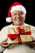 grey-haired man offering golden wrapped present - stock photo