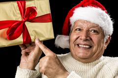 Excited aged man pointing at golden gift in hand Stock Photos