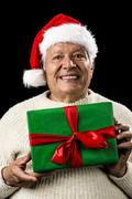 male senior with santa claus cap and green gift - stock photo