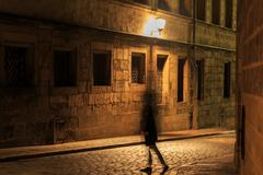 Girl silhouette in motion on night illuminated street Stock Photos