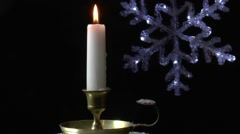 A burning candle is turning against a black background Stock Footage