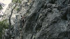 Rock climber does difficult move Stock Footage