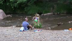 Father and daughter throwing rocks into river Stock Footage