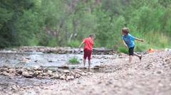 Boys throwing rocks in river Stock Footage