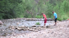 Boys throwing rocks in river 02 Stock Footage