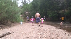 Father walking daughters on riverbed Stock Footage