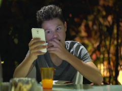 Young teenager eating sandwich and using  smartphone at home at night NTSC Stock Footage