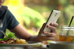 Teenager hands sending sms, texting on smartphone in restaurant NTSC - stock footage